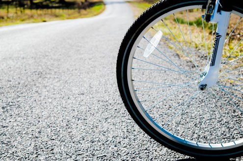 Photo of bicycle wheel on gravel rural road