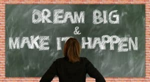 "Photo of woman staring at chalkboard stating ""Dream Big and Make it Happen"""